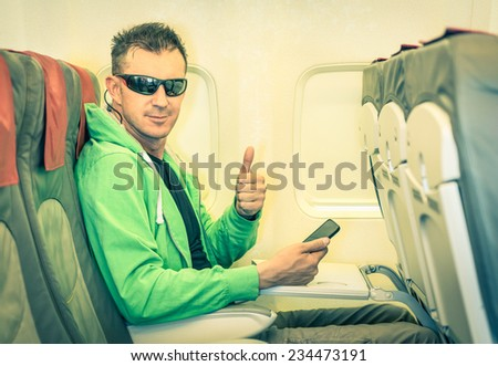 Young hipster man passenger satisfied with thumbs up after boarding - Concept of low coast flight and connection with modern technologies on board - Alternative lifestyle traveling around the world - stock photo