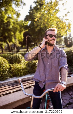 Young hipster man riding vintage bike on city street and talking on the phone - stock photo