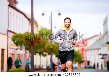 Young hipster man running in town, main street
