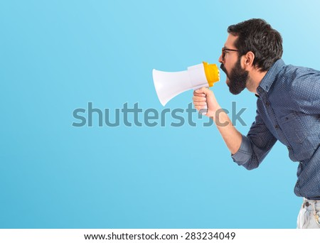 Young hipster man shouting by megaphone over colorful background
