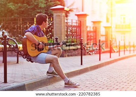 Young hipster man sitting during sunshine with acoustic guitar while dreaming  - stock photo