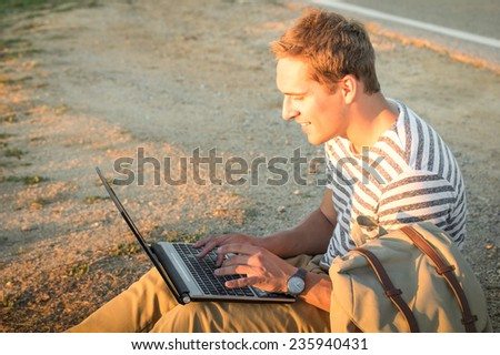 Young hipster man sitting outdoors checking mails on modern laptop computer - Concept of technology and connection in nature environment - Internet wifi communication - stock photo