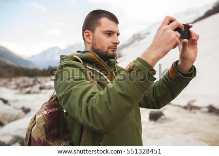 young hipster man, taking pictures using smartphone, wild nature, winter vacation, hiking, traveling, backpacker, warm clothes