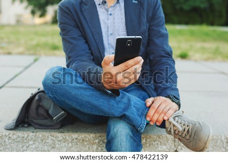 Young hipster man using smart phone sitting outdoor