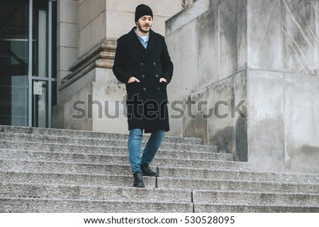 Young hipster man walking down the stairs with hands in the pockets in front of large column wall