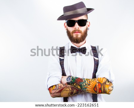 young hipster man wearing  hat , suspenders,  bow-tie and a funny tattoo-sleeve - stock photo