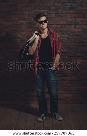 Young hipster man wearing sunglasses casual clothes unbuttoned shirt and denim jeans with bag over shoulder standing near brick wall with hand in the pocket and looking away. - stock photo
