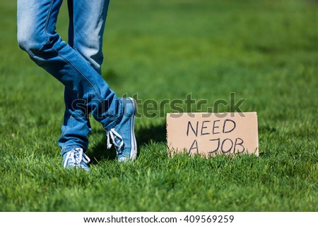 "Young hipster man with ""need a job"" sign, unemployment concept"