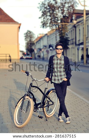 Young hipster man with retro bike