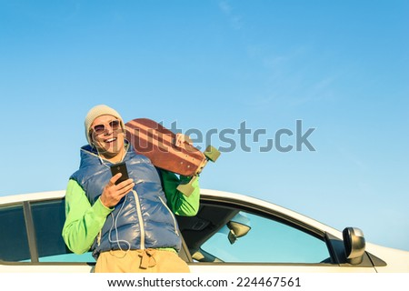 Young hipster man with smartphone listening music next his car - Concept of modern technologies mixed with a vintage travel lifestyle - Autumn winter youth alternative fashion in a sunny day trip - stock photo