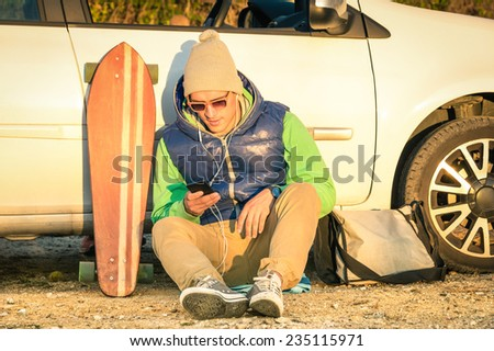 Young hipster man with smartphone sitting next his car with winter fashion clothes - Concept of modern technologies mixed with a vintage lifestyle - Warm colors at sunset - stock photo