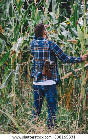 Young hipster man with vintage camera in a corn filed. Vintage retro style effect, soft focus, shallow DOF, low light, grain texture visible on maximum size - stock photo