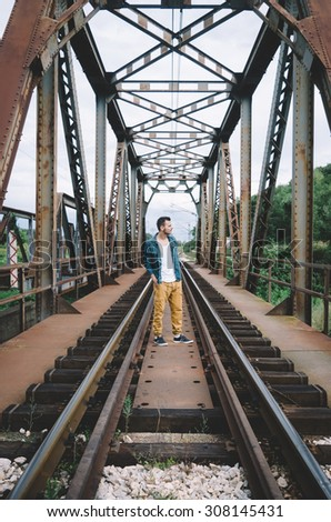 Young hipster posing standing on the railroad bridge. Vintage Instagram style effect, soft and selective focus, shallow DOF, low light, grain texture visible on maximum size - stock photo