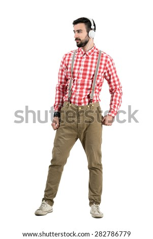 Young hipster posing with headphones looking away.  Full body length portrait isolated over white background.  - stock photo