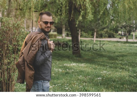 Young hipster posing with leather jacket