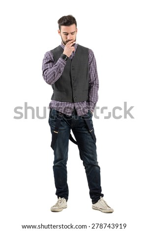 Young hipster smoking cigarette looking down. Full body length portrait isolated over white background.  - stock photo