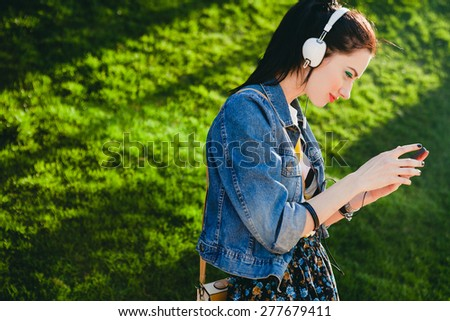young hipster stylish beautiful girl listening to music, mobile phone, headphones, enjoying, denim outfit, smiling, happy, cool accessories, vintage style, having fun, looking, park - stock photo