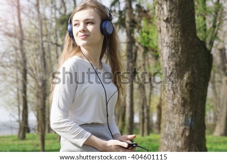young hipster stylish beautiful girl listening to music, mobile phone, headphones, enjoying,  denim outfit, smiling, happy, cool accessories, vintage style, having fun, laughing, park - stock photo