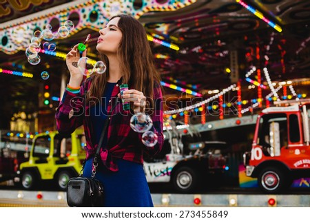 young hipster stylish beautiful woman blowing soap bubbles dressed in blue dress and checkered shirt at the amusement park, enjoying the summer day, fun, joy, happiness - stock photo