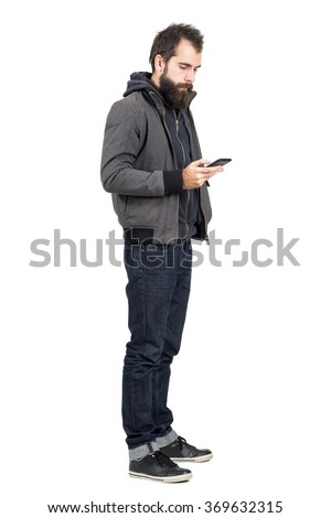 Young hipster wearing jacket over hooded sweatshirt typing on mobile phone.  Full body length portrait isolated over white studio background.  - stock photo