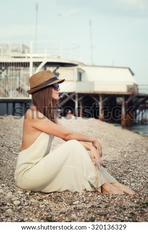 Young hipster woman dressed in white dress and hat sitting on a seacoast. - stock photo