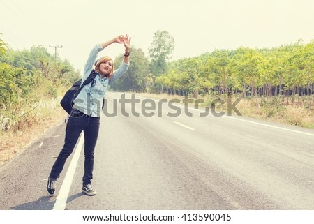 young hipster woman hitchhiking on countryside road looking for the car - stock photo