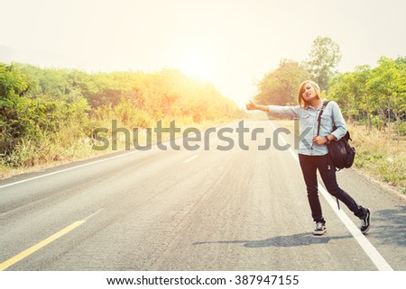 young hipster woman hitchhiking on countryside road wait for the car  - stock photo