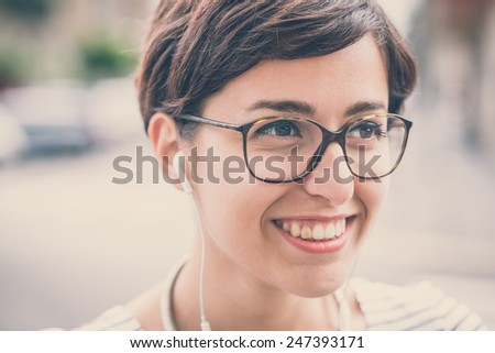 young hipster woman listening to music in the city - stock photo
