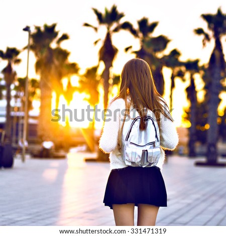 Young hipster woman posing on California beach at sunset, sunny autumn time, wearing trendy faux fur jacket and mini skirt, student with backpack, bright toned colors. - stock photo