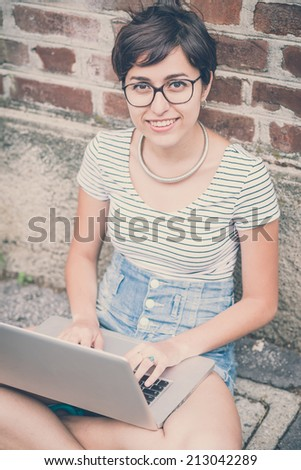 young hipster woman using notebook in the city