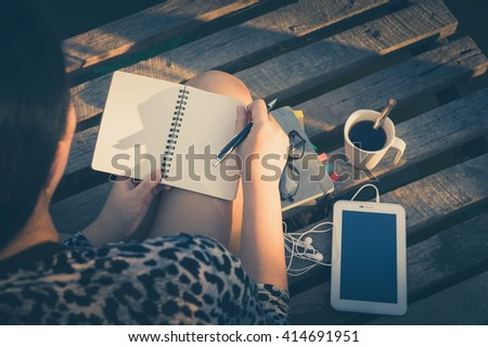 Young hipster woman writing journal on small notebook while sitting on wood bridge in early morning time on weekend with high contrast sun lighting and vintage filter effect - stock photo