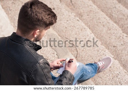 Young hipster writing something in his notebook - stock photo