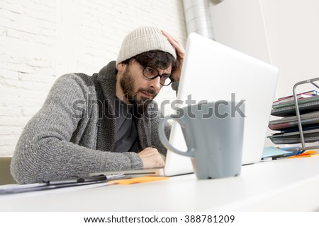 young hispanic attractive  hipster 30s businessman working busy at modern home office with computer laptop dressing casual  beanie in creative freelancer business success concept - stock photo