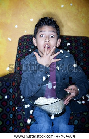 Young Hispanic boy with popcorn watching television - stock photo