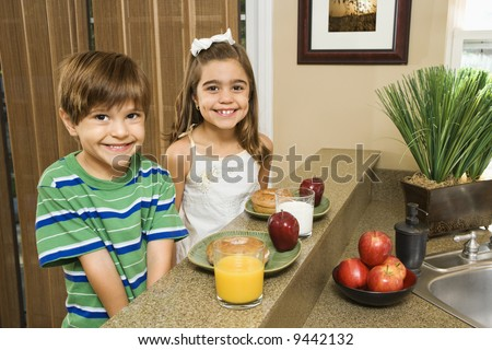 Young Hispanic brother and sister sitting at kitchen bar with healthy breakfast smiling at viewer. - stock photo