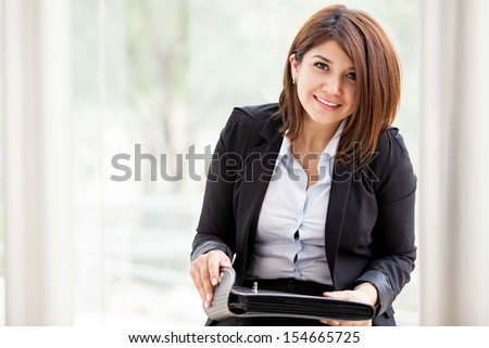 Young Hispanic businesswoman opening a briefcase and smiling