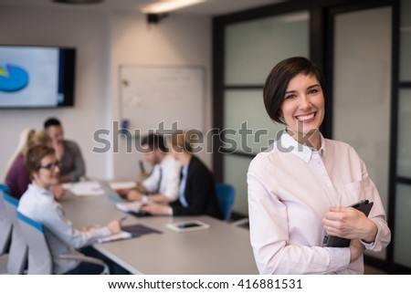 young hispanic businesswoman portrait with  tablet computer at modern startup business office interior, people group on team meeting blured in background - stock photo