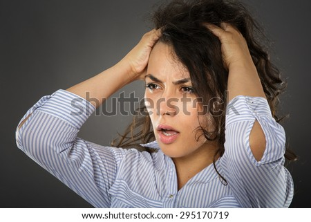 Young hispanic businesswoman with a shock expression, just after making a catastrophic mistake in her work - stock photo