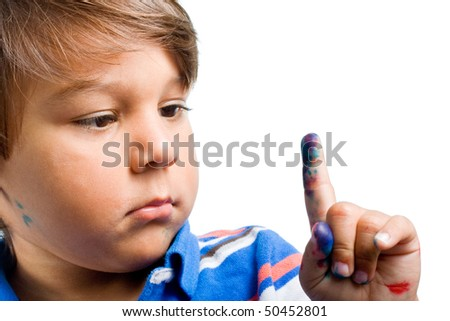 Young Hispanic child looking at his painted finger, closeup portrait isolated on white background - stock photo