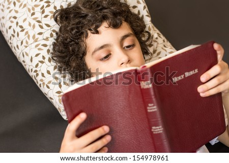 Young Hispanic child reading and studying the Holy Bible at home. Daily devotional and reverence of a boy. Taking a break and meditating on the word of God. Love of a child for his Creator in Heaven - stock photo