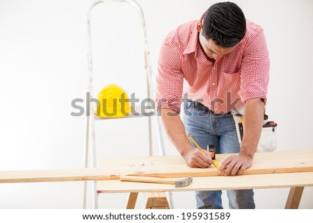 Young Hispanic contractor measuring a wood board before cutting it