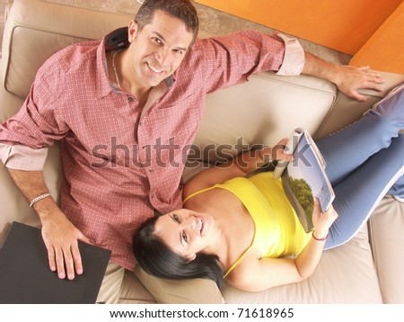 Young hispanic couple enjoying in a living room. Young couple enjoying in a house. - stock photo