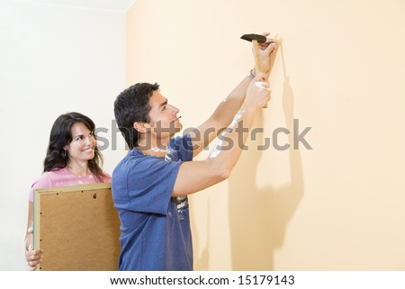 Young Hispanic couple hanging picture on wall - stock photo