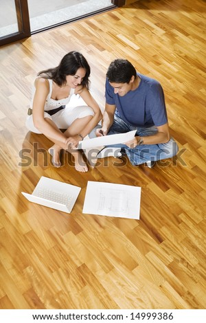 Young Hispanic couple looking at blueprints of new home, high angle view - stock photo