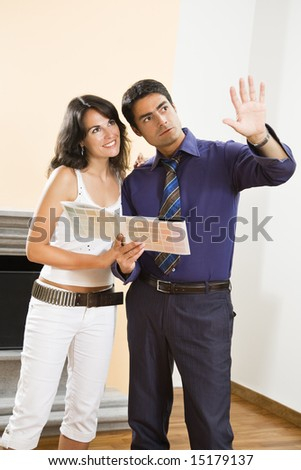 Young Hispanic couple looking at paint swatches for new home - stock photo