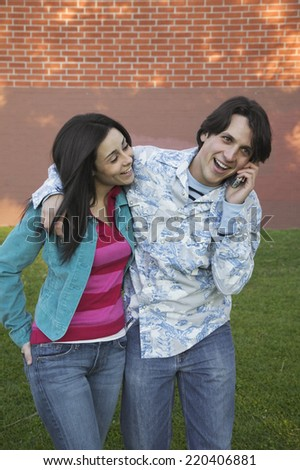 Young Hispanic couple using cell phone outdoors - stock photo