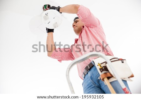 Young Hispanic electrician wiring a lamp fixture on the ceiling