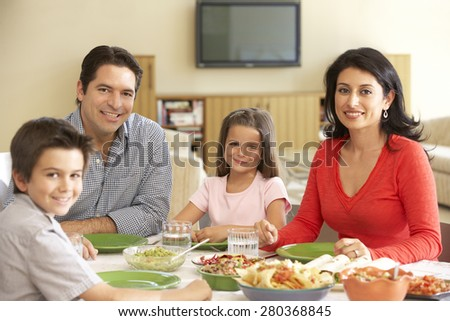 Young Hispanic Family Enjoying Meal At Home - stock photo