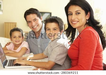 Young Hispanic Family Using Computer At Home - stock photo