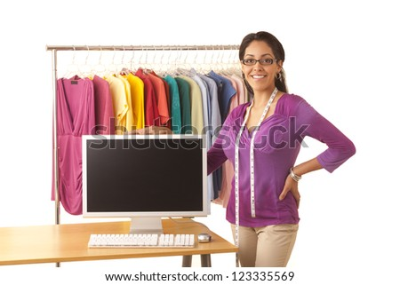 Young Hispanic fashion designer standing at work table with computer - stock photo